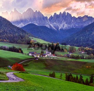 Autumn daybreak Santa Magdalena famous Italy Dolomites village view in front of the Geisler or Odle Dolomites mountain rocks.