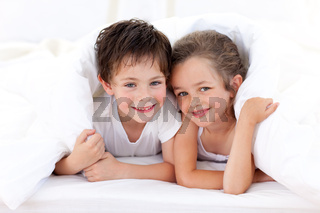 Brother and sister playing on parent's bed