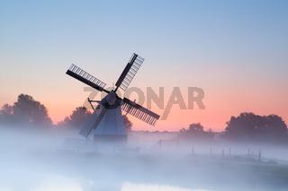 charming Dutch windmill in morning fog