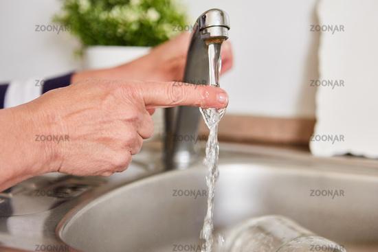 Finger unter dem fließenden Wasser am Wasserhahn