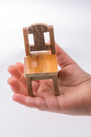 Brown color wooden toy chair in hand