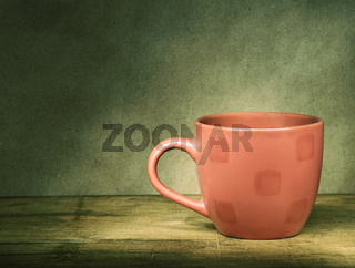 Red cup on a wooden table.