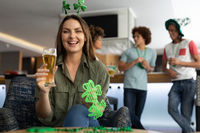 Portrait of caucasian woman wearing deely boppers and holding beer celebrating st patrick's at a bar
