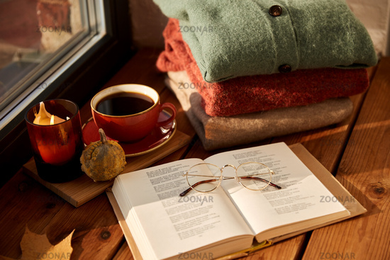 book, coffee and autumn sweaters on window sill