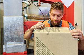 Kommissionierer kontrolliert Paket im Wareneingang