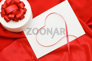 Box with a gift on a red fabric