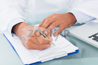 Hand of a doctor writing on a prescription