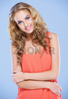 Confident young lady with folded arms smiling at the camera