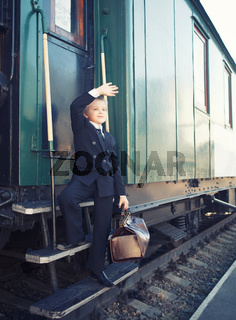 little boy with a suitcase in the retro train