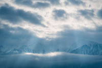 Winter mountains covered with snow between clouds with bright sunrays shining through, Mieminger Plateau, Tirol, Austria