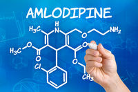 Hand with pen drawing the chemical formula of Amlodipine