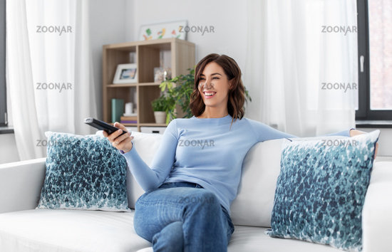 happy woman watching tv at home