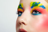 Close-up of teenager girl portrait with unusual face art make-up with paint on brows.