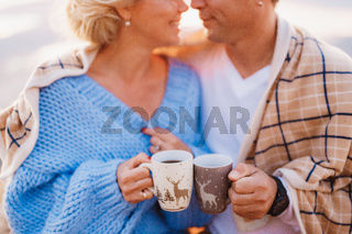 Smiling couple wrapped in a plaid and holding cups in their hands on a background of mountains