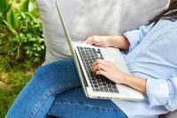 Freelancer oder Programmierer am Laptop im Garten