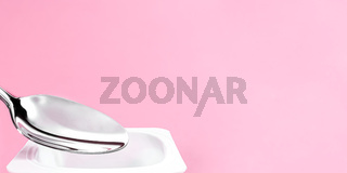 Yogurt cup and silver spoon on pink background, white plastic container with yoghurt cream, fresh dairy product for healthy diet and nutrition balance