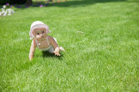 Beautiful little girl crawling on the grass