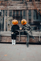 Guy and girl with pumpkin heads in a street cafe holding hands