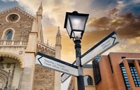 Lantern and tourist signpost in centre of Madrid city at sunset. Spain