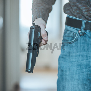 Police undercover weapon concept: Man is holding black weapon in his hand