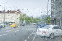 Car Driving In A Rain Storm With Blurred city view. View from car at raining day