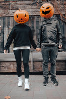 A guy and a girl with a pumpkin heads. Couple holding hands