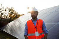 Worker in a vest and helmet stands on a solar station