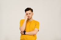 Lost in thought or deep in thought handsome young man folded his hands and holding his face with his hand. Young casual man in yellow t-shirt portrait isolated on white background
