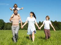 Family walking on summer meadow