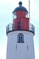 Top of a lighthouse against a blue sky. Red and black metal, window with bars. Background