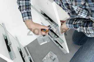 Close up of a Man Assembling a drawer slider Furniture using a screwdriver