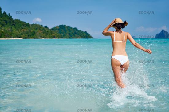 Happy slim woman running into the sea enjoy her tropical beach vacation, having fun and splashing water