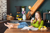 Young woman reading an interesting magazine at wooden table