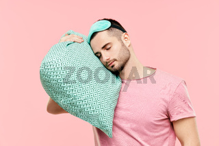Young handsome man sleeping holding pillow in hands