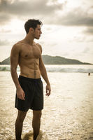 Young man standing on edge of the ocean