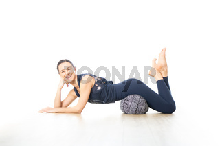 Restorative yoga with a bolster. Young sporty female yoga instructor in bright white yoga studio, lying on bolster cushion, stretching, smilling, showing love and passion for restorative yoga