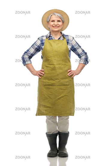 smiling senior woman in garden apron and straw hat