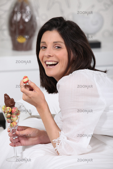 Laughing woman with a glass of mini Easter eggs