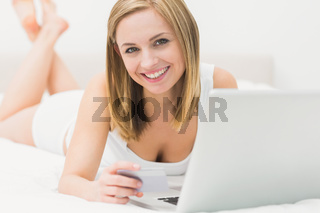 Portrait of woman doing online shopping in bed