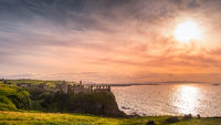 Sunset at ruins of Dunluce Castle, perched on the cliff, Northern Ireland