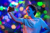 woman taking selfie with smartphone in neon lights