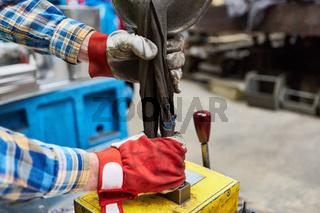 Arbeiter mit Handschuhen befestigt Last an Kranhaken