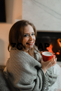 the woman with hot drink relaxes by the fireplace