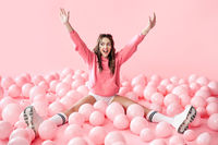 Young happy woman with hands up sitting in pink balloons on pastel pink background