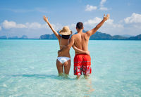 Rear view of happy couple with hads up enjoying their paradise beach vacation