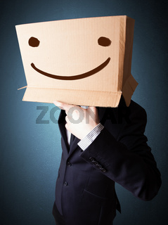 Businessman gesturing with a cardboard box on his head with smiley face