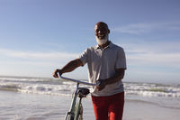Senior african american man with bicycle smiling while walking together on the beach