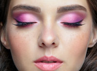 Closeup portrait of female face with pink lips and smoky eyes beauty makeup.