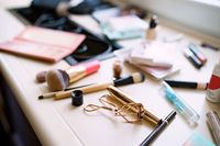 Makeup artist set. Close-up of eyelash curler and mascara in golden packaging with makeup brushes on a blurred window sill background.