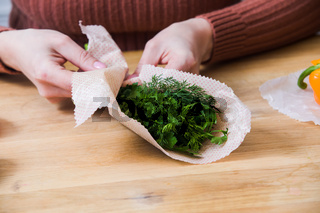 Female wrapping green dill and parsley into beeswax wraps